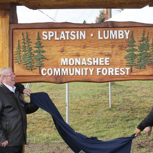 A new sign is unveiled Tuesday by Rick Fairbairn (left), Monashee Community Forest president, MLA Eric Foster, Lumby Mayor Kevin Acton and Splatsin Chief Wayne Christian.— Image Credit: Richard Rolke/Morning Star